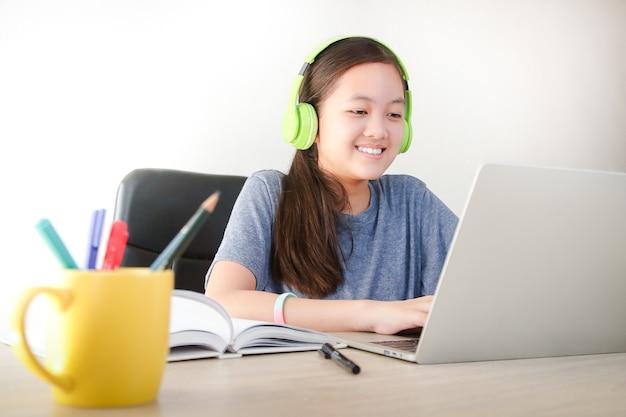 Las niñas asiáticas estudian en línea desde casa mediante videollamadas. utilizan una computadora portátil para comunicarse con los maestros. concepto educativo, distanciamiento social para reducir la propagación del coronavirus (covid-19)