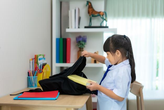 Niñas asiáticas lindas de la escuela primaria que empacan la mochila escolar
