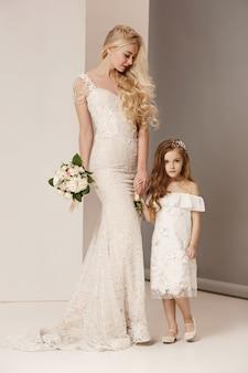Niñas bonitas con flores vestidas con vestidos de novia