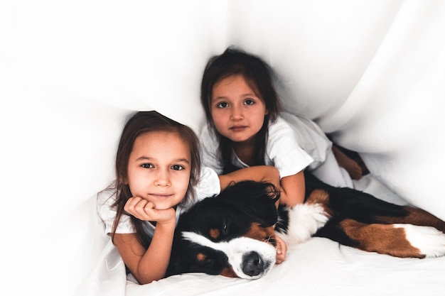 Niñas en la cama con perro bernese mountain dog, amistad