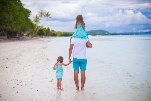 Niñas caminando con papá en una playa tropical
