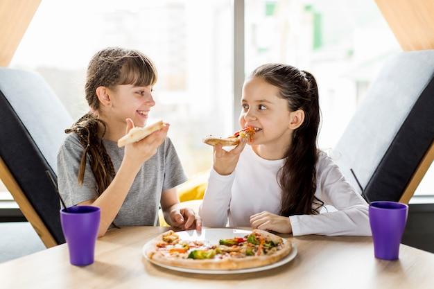 Niñas comiendo pizza