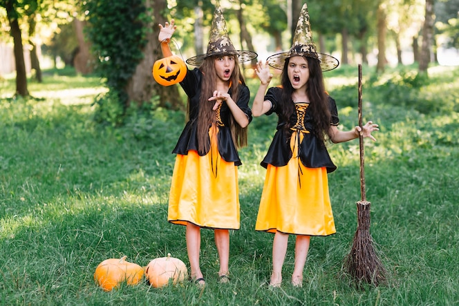 Niñas con disfraces de bruja mostrando manos extendidas