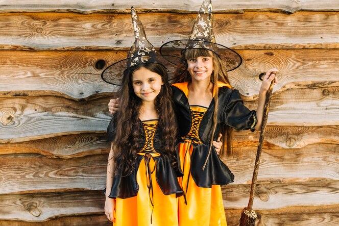 Niñas con trajes de bruja abrazándose y sonriendo