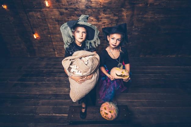 Niñas disfraces de brujas con calabazas y golosinas en halloween en un escenario de madera