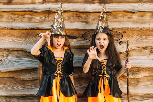 Niñas en disfraces de brujas de halloween fingiendo hechizo