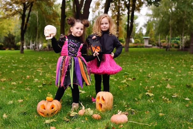 Niñas en disfraces de halloween con calabazas para halloween