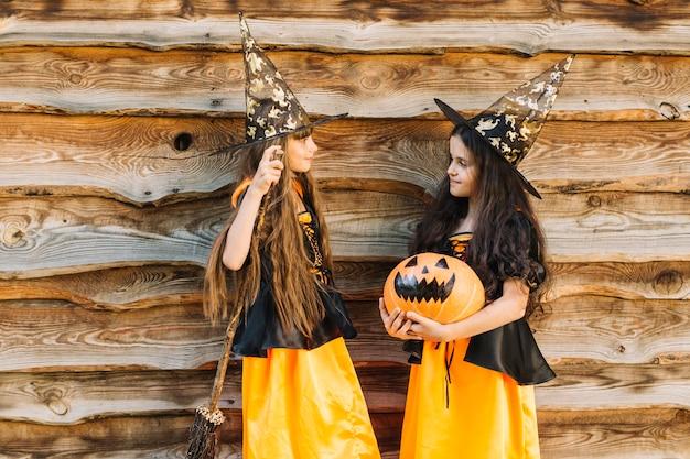 Niñas en disfraces de halloween con escoba y calabaza mirándose
