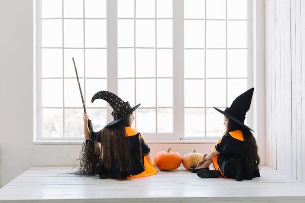Niñas en disfraces de halloween con escoba mirándose entre sí cerca de la ventana