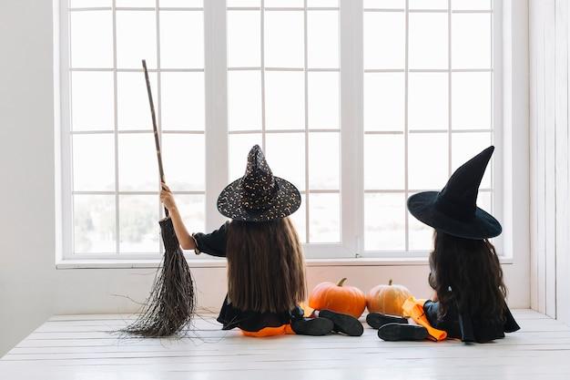 Niñas en disfraces de halloween con escoba sentada junto a la ventana