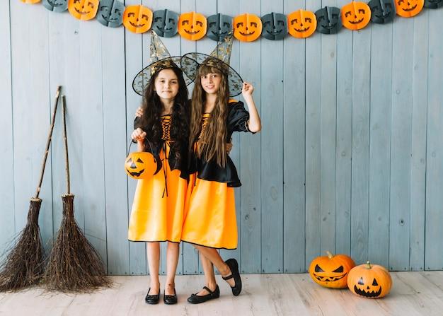 Niñas en disfraces de halloween con sombreros puntiagudos de pie abrazando
