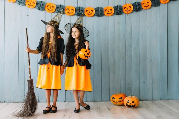 Niñas en disfraces de halloween tomados de la mano y mirando a otro lado