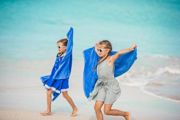 Las niñas se divierten con una toalla de playa durante las vacaciones tropicales