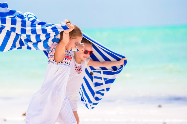 Niñas divirtiéndose corriendo con toallas en la playa tropical. los niños disfrutan de sus vacaciones de verano familiares en el océano índico
