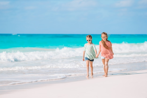 Niñas divirtiéndose en la playa tropical jugando juntos en aguas poco profundas