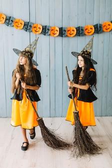 Niñas en ropa de hechicera sosteniendo palos de escoba