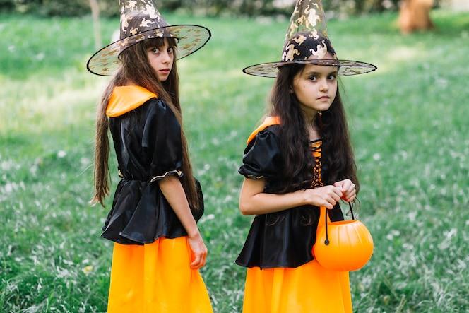 Niñas en trajes de hechicera apostados en el parque