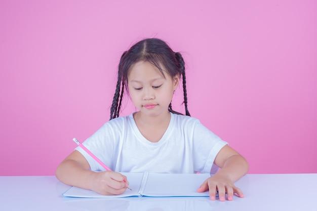 Las niñas escriben libros sobre un fondo rosa.