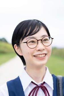 Niñas de la escuela secundaria asiática vistiendo uniformes y sonriendo en la escuela