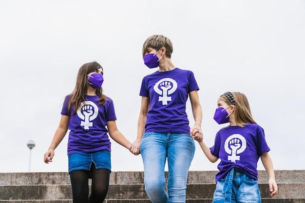 Niñas de una familia vistiendo una camiseta morada con el símbolo de la mujer trabajadora que reclama los derechos de la mujer para el día internacional de la mujer el 8 de marzo y con una mascarilla por el coronavirus.