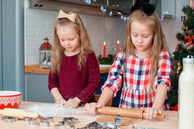 Niñas felices adorables que hornean galletas de jengibre de navidad en la víspera de navidad