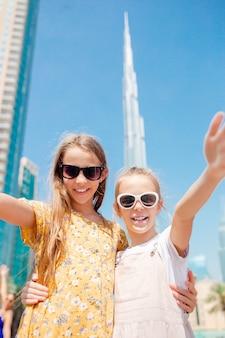 Niñas felices caminando en dubai con rascacielos