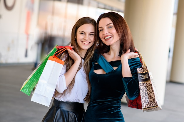 Las niñas felices están comprando en el centro comercial.