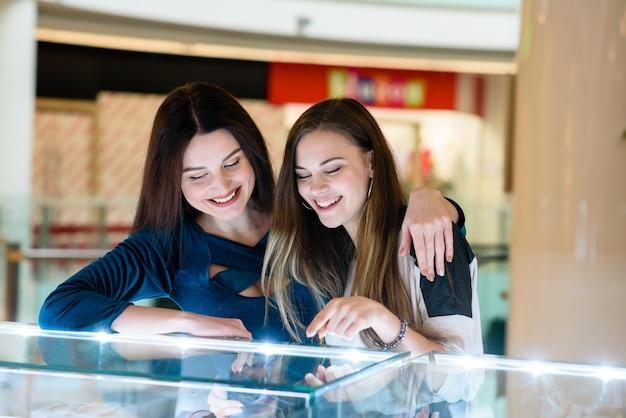 Las niñas felices están de compras en el centro comercial.