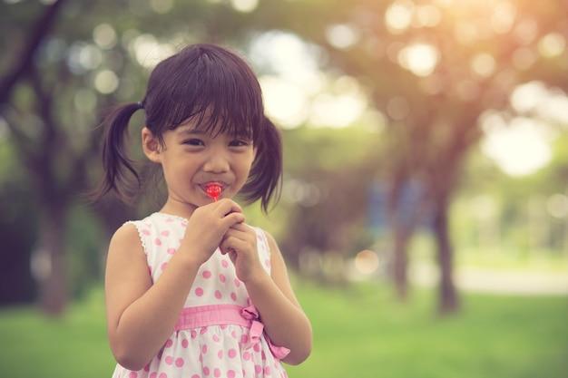 Niñas felices con piruletas al aire libre. color vintage