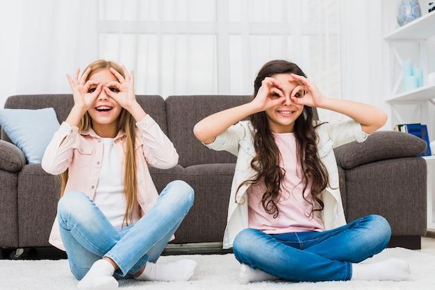 Niñas felices sentadas en la alfombra haciendo un gesto aceptable como binoculares