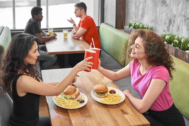 Niñas felices sentados en la cafetería de comida rápida, tintineando vasos de papel.