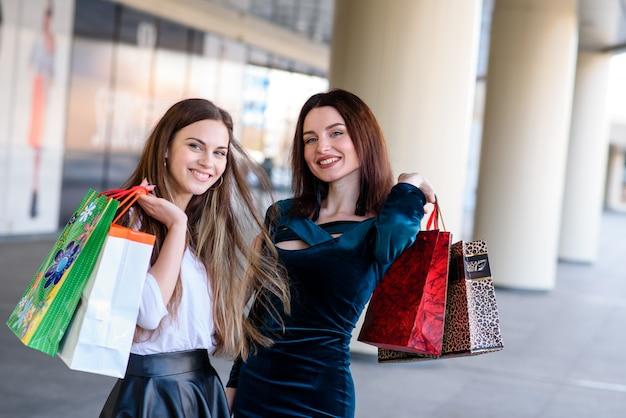Niñas felices sonriendo y haciendo compras en el centro comercial.
