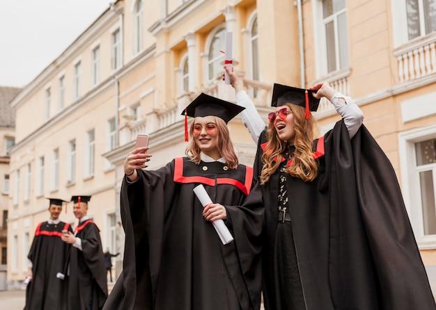 Niñas felices tomando selfie con diploma