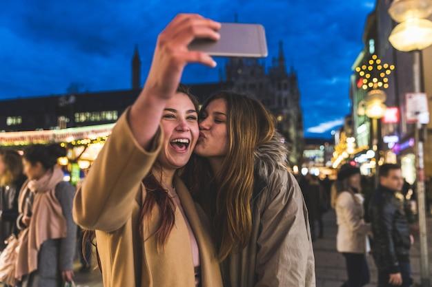 Niñas felices tomando un selfie juntos en el mercado de navidad de munich