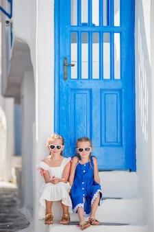 Niñas felices en vestidos en la calle de un pueblo tradicional griego típico en la isla de mykonos, en grecia