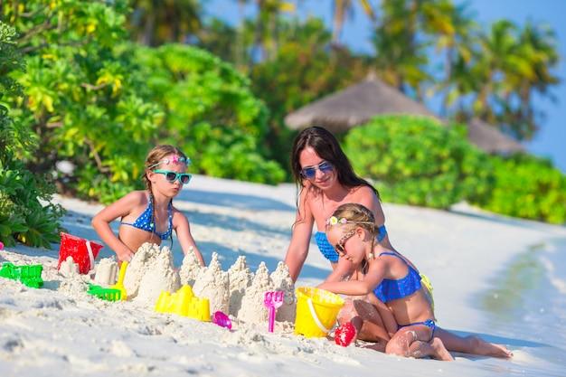 Niñas y feliz madre jugando con juguetes de playa en vacaciones de verano