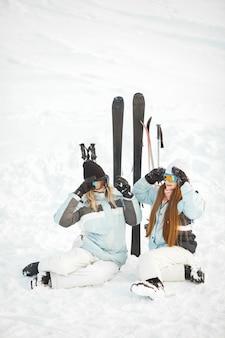Las niñas se fueron a esquiar en la nieve. divirtiéndose al ser fotografiado. pasa tiempo en las montañas.