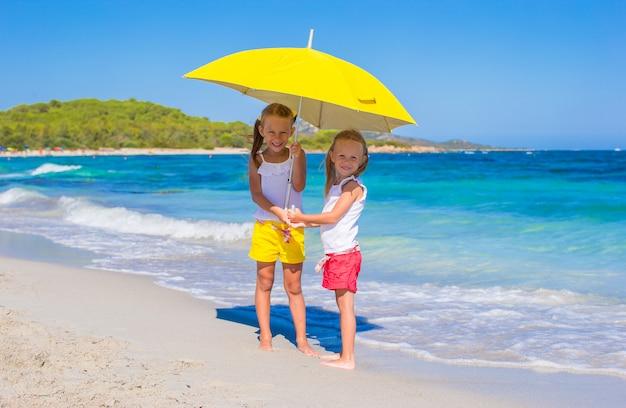 Niñas con gran sombrilla amarilla caminando en la playa tropical