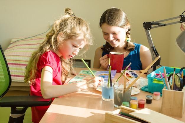Niñas hermanas en casa en la mesa pintan con acuarela.