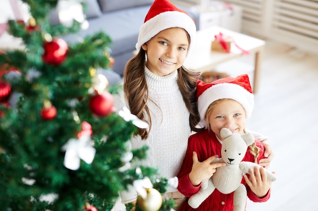 Niñas hermanas felices y árbol de navidad decorado en el salón interior
