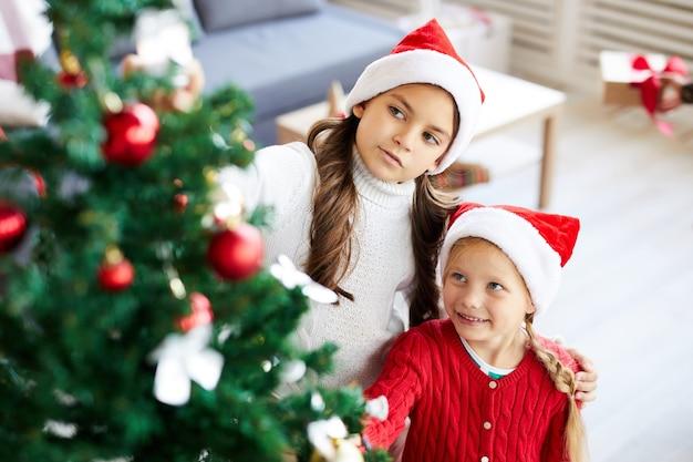 Niñas hermanas felices mirando el árbol de navidad decorado en el salón interior