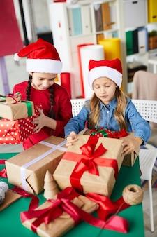 Niñas hermanas felices con regalos de navidad
