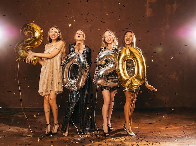 Niñas hermosas felices en elegantes vestidos de fiesta sexy con globos dorados y plateados 2020