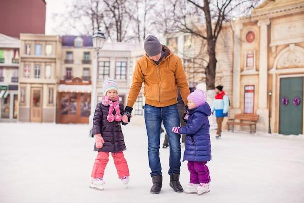 Niñas con joven padre disfrutando del patinaje
