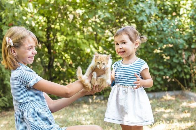 Las niñas juegan con gatito al aire libre en el parque.