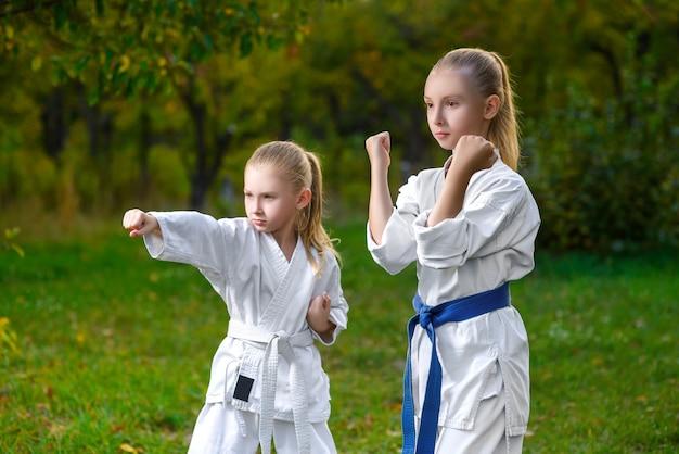 Niñas en kimono blanco durante el entrenamiento de ejercicios de karate en verano al aire libre