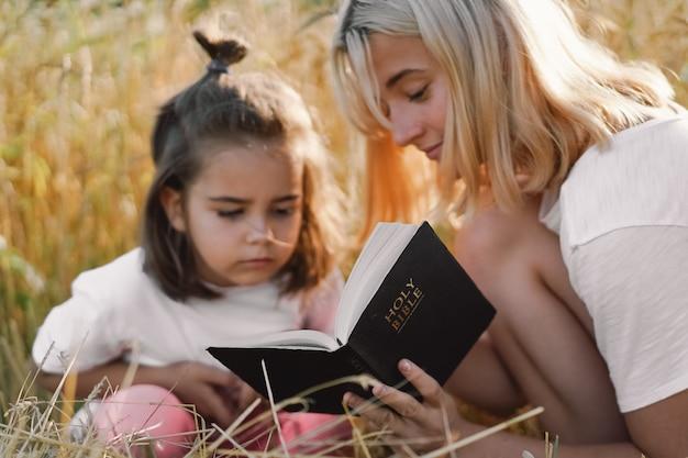 Niñas leyendo la santa biblia en un campo de trigo. estudien la santa biblia juntos.