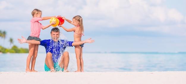 Niñas lindas divirtiéndose con papá en la playa blanca