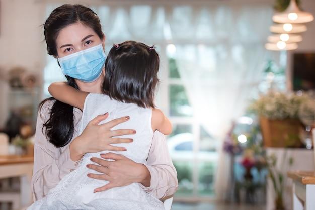 Niñas y madres asiáticas con máscaras médicas abrazándose