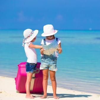 Niñas con maleta grande y mapa en playa tropical